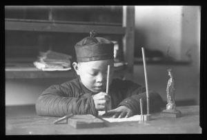 Boy_seated_at_a_table_writing,_China,_ca._1918-1938_(MFB-LS0248B)-2